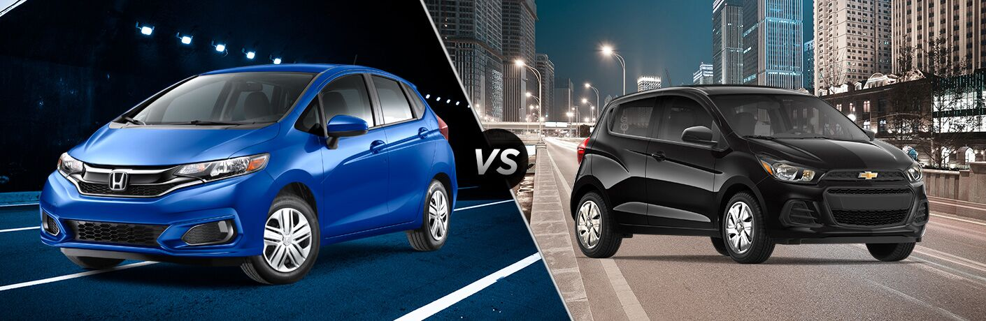 2018 Honda Fit exterior front fascia and drivers side on road at night vs 2018 Chevy Spark on city road at night