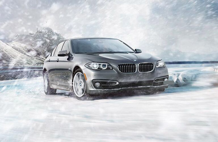 grey 2016 BMW 5 Series driving in the snow