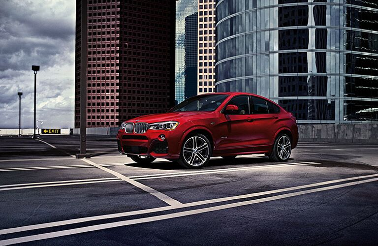 Red 2016 BMW X4 on a city road
