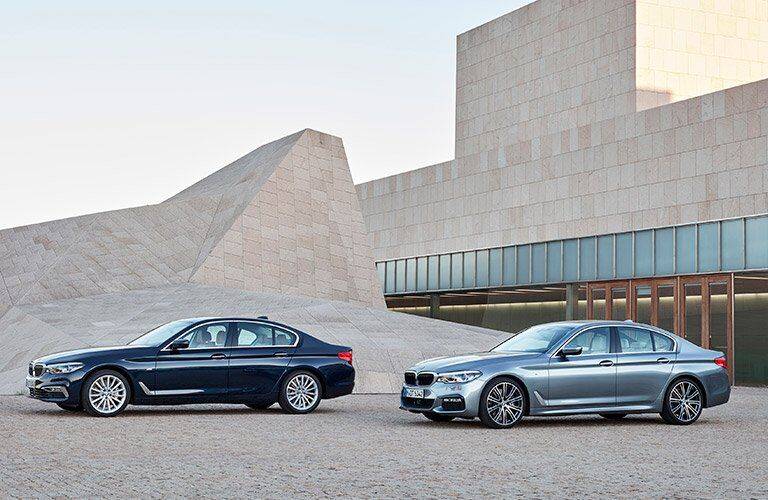 Two 2017 BMW 5 Series Parked In Front Of A House