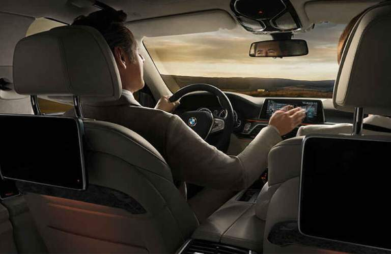 driver in the front seats of the 2018 BMW 7 Series using the infotainment system