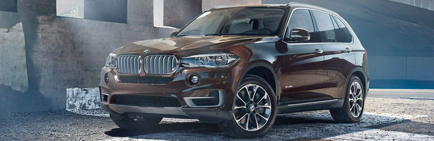 brown 2018 BMW X5 in front of a stone wall