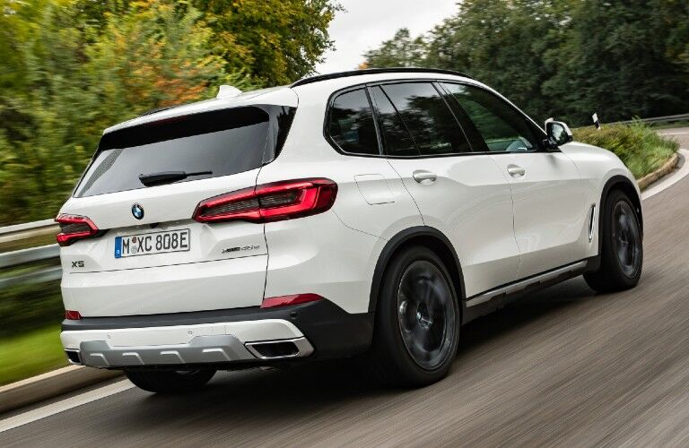 2021 BMW X5 driving through curve in road