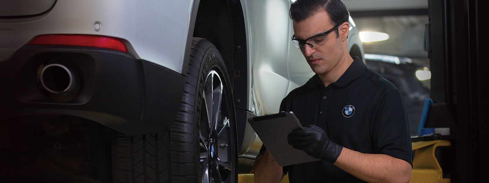 BMW Service Technician in service bay inspecting a BMW on a lift.