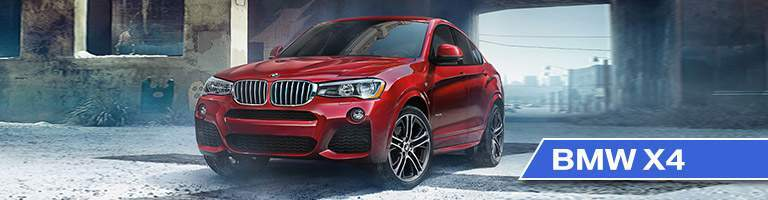 red 2017 BMW X4 parked with a vague town in the background