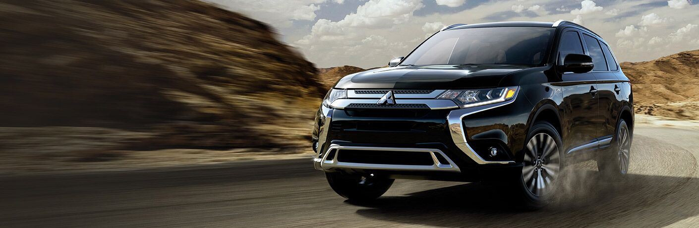 Black Mitsubishi Outlander winds its way through a desert road.