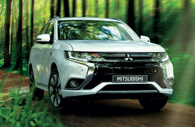 White Mitsubishi Outlander PHEV drives through a forest on a dirt path.