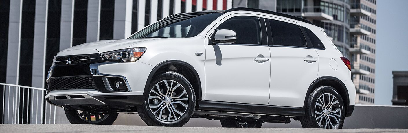White 2018 Mitsubishi Outlander Sport parked in an urban center.