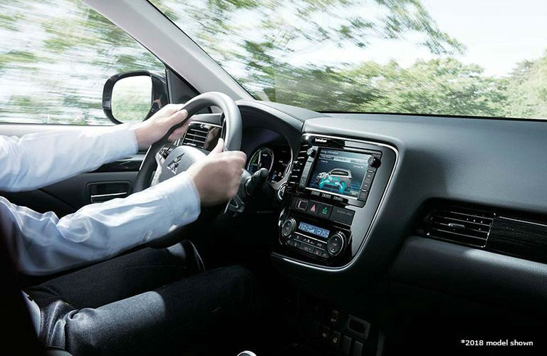 A businessman grips the wheel as he cruises among trees in his 2018 Mitsubishi Outlander PHEV.