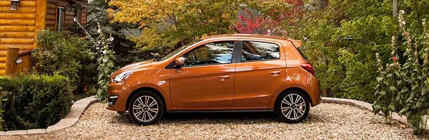 Side view of an orange 2020 Mitsubishi Mirage parked by a log cabin.