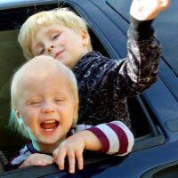 Two children laugh and wave from the window of their vehicle.