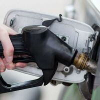 A hand holds a fuel pump in a gas tank opening.