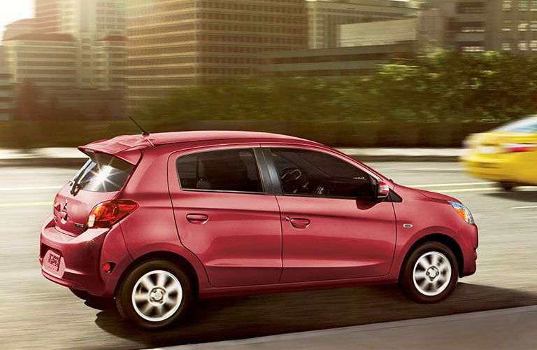 Rose-colored Mitsubishi Mirage cruises along a city highway.