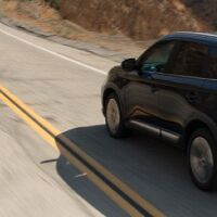 Front half of a black Mitsubishi Outlander driving up a desert road.