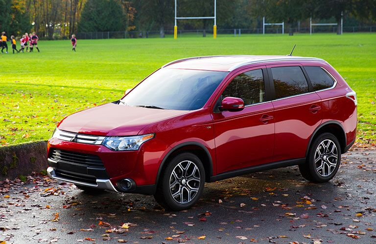 Red Mitsubishi Outlander parked near a childrens' football game.
