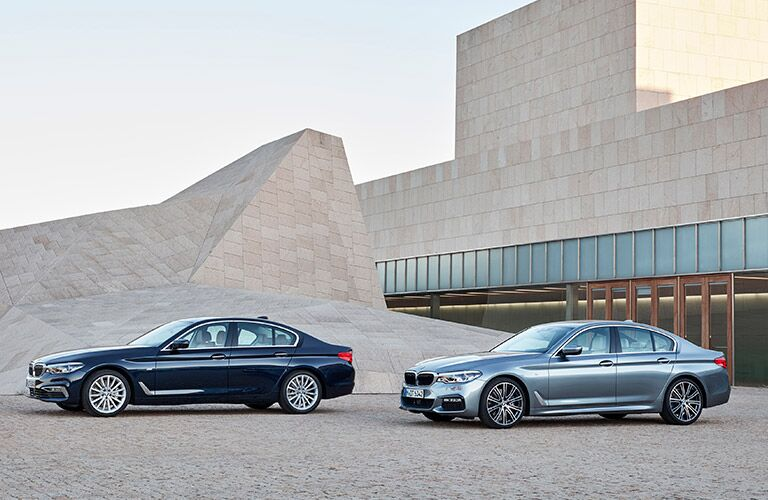 two 2017 BMW 5 Series sedans parked in front of a modernist sand-colored house