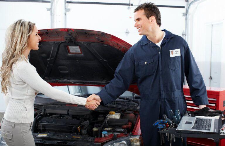 mechanic and female customer shaking hands