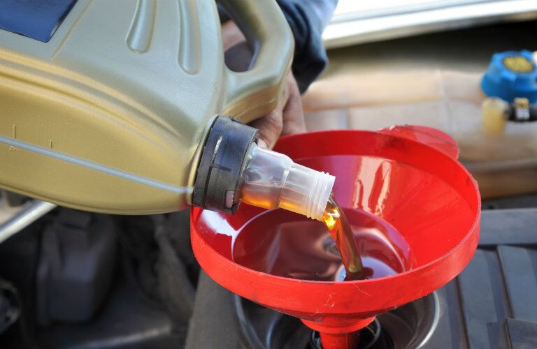mechanic pouring oil into a vehicle
