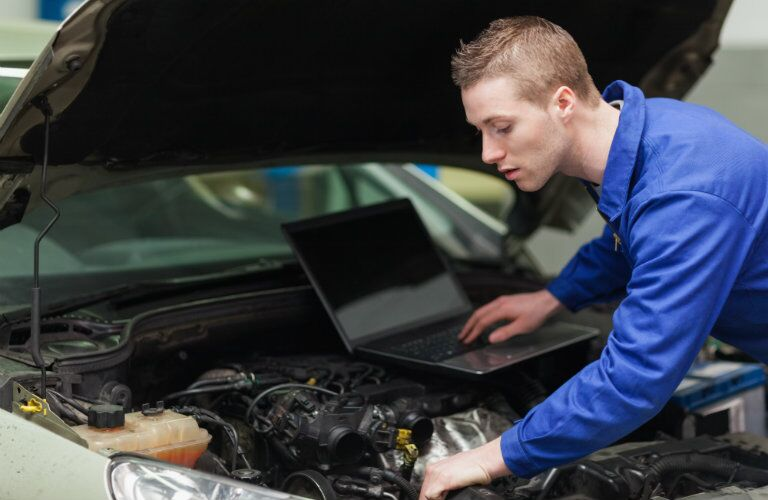 technician using computer to help check under car hood
