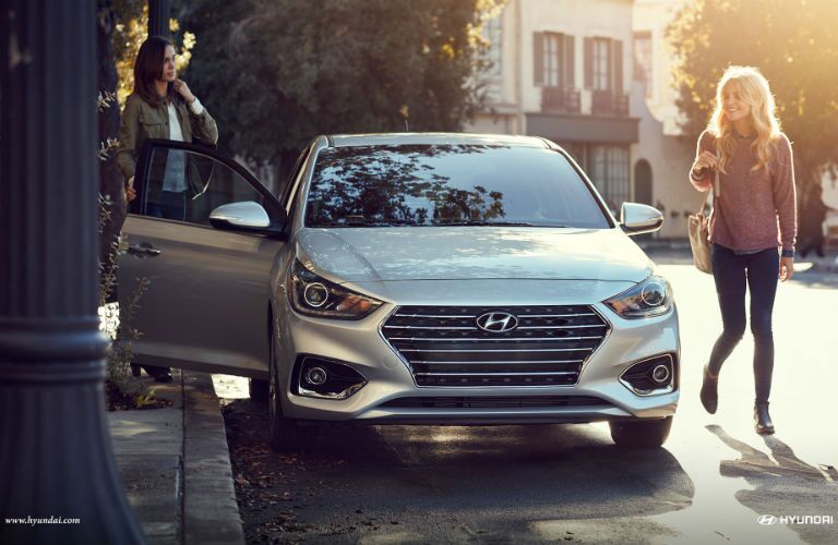 Two women standing on either side of 2018 Hyundai Accent