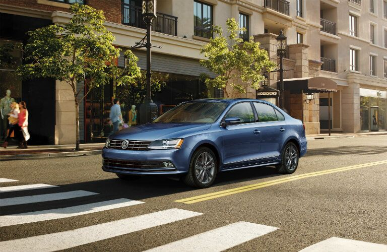 Long view of blue 2018 Volkswagen Jetta parked in front of tree-lined building