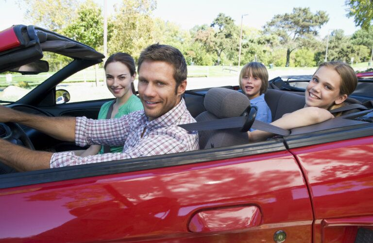 Family smiling while they are driving in a red convertible