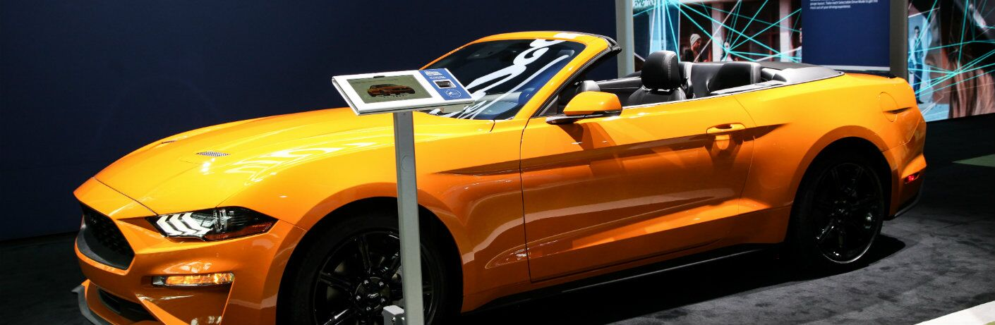 Yellow Ford Mustang Convertible in a showroom