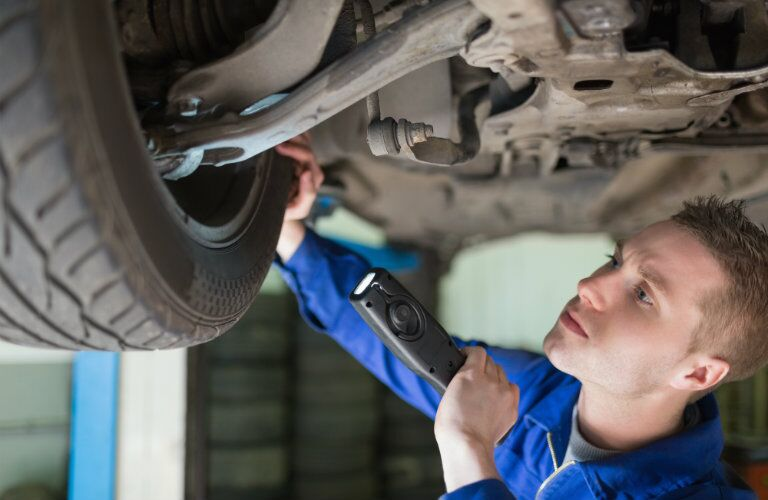 mechanic inspecting tire and wheel of car