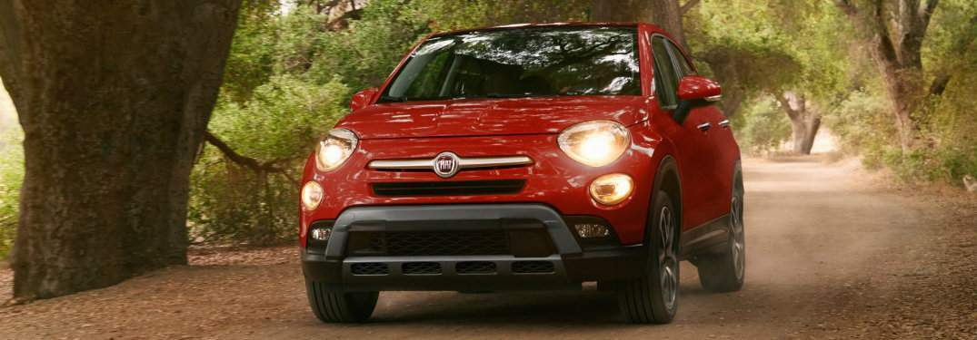Red Fiat driving through wooded area