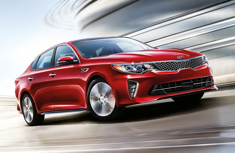 red Kia Optima driving