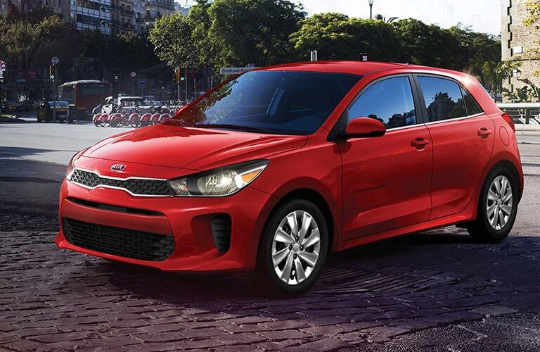 2019 Kia Rio hatchback exterior shot with red paint color parked on a stone tile road outside