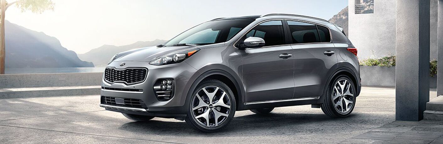 2019 Kia Sportage exterior shot with gray paint job parked outside a columned garage in a mountain house