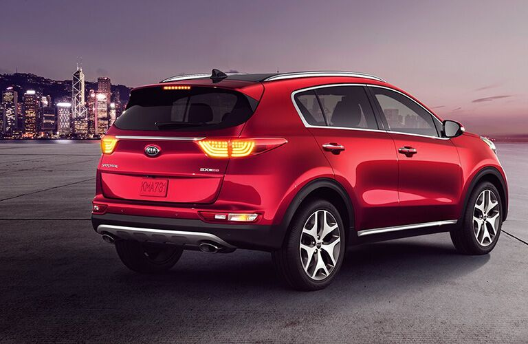 2019 Kia Sportage exterior rear shot with red paint job parked on a concrete lot with a night lit cityscape skyline in the background