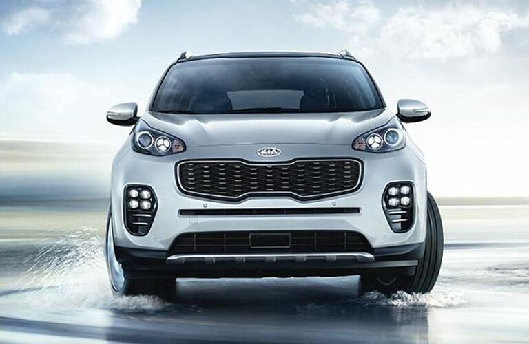 2019 Kia Sportage exterior front shot of grille and headlights as it turns through a flooded landscape