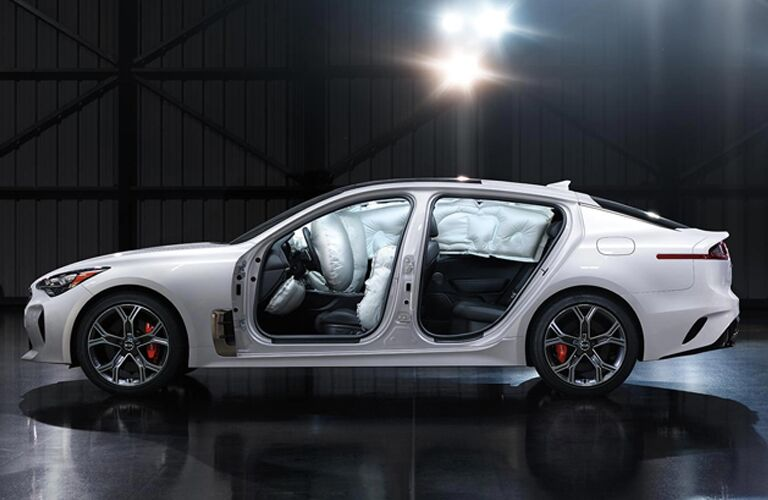 2019 Kia Stinger exterior side shot frame with white paint color and deployed airbags in an empty showroom