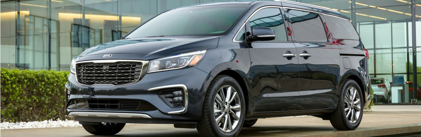 2019 Kia Sedona exterior shot with black paint color parked outside a glass Kia dealership building next to a row of bushes