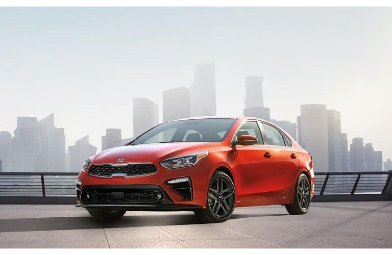 2019 Kia Forte exterior shot with red paint color parked on a cement pier with a foggy cityscape behind it