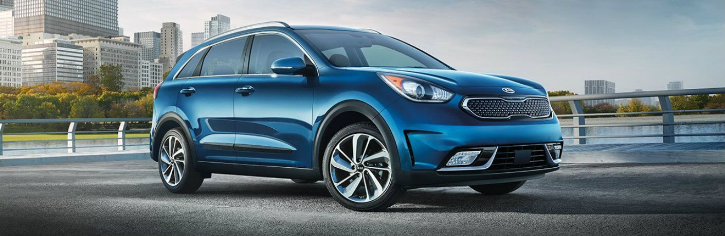 2019 Kia Niro exterior shot with light blue paint color parked near a lake with a forest and city skyscraper background