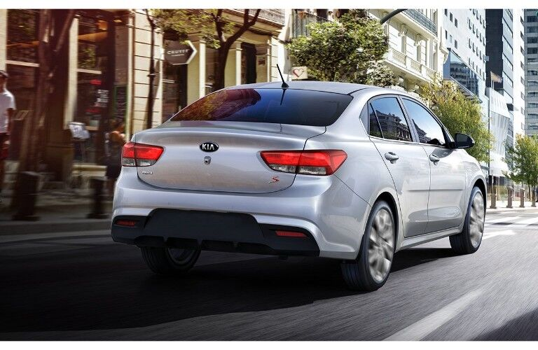 2019 Kia Rio exterior rear shot with gray paint color driving through a city near a cafe sidewalk and skyscrapers