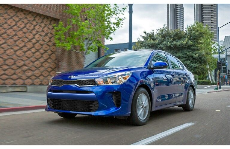 2019 Kia Rio exterior shot with blue paint color driving through a spacious downtown area near a red brick building