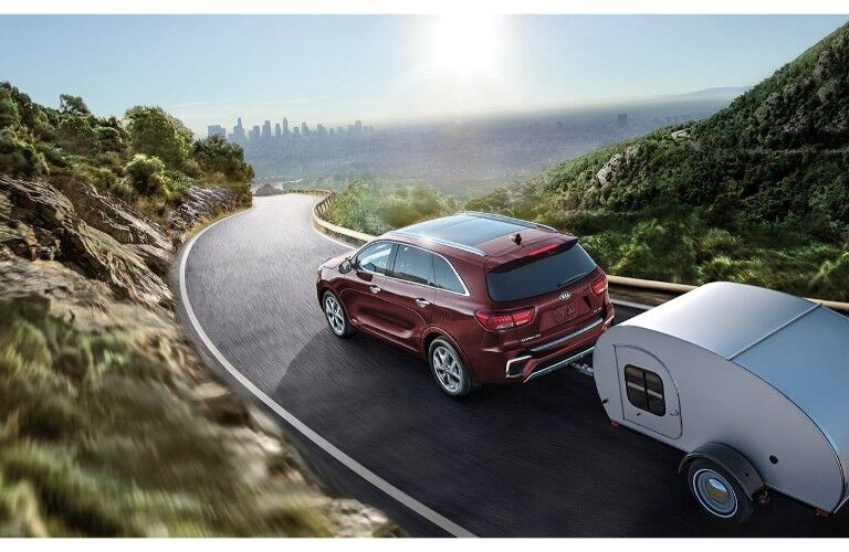 2019 Kia Sorento exterior overhead shot with red paint color towing a trailer through a grassy mountain hill path