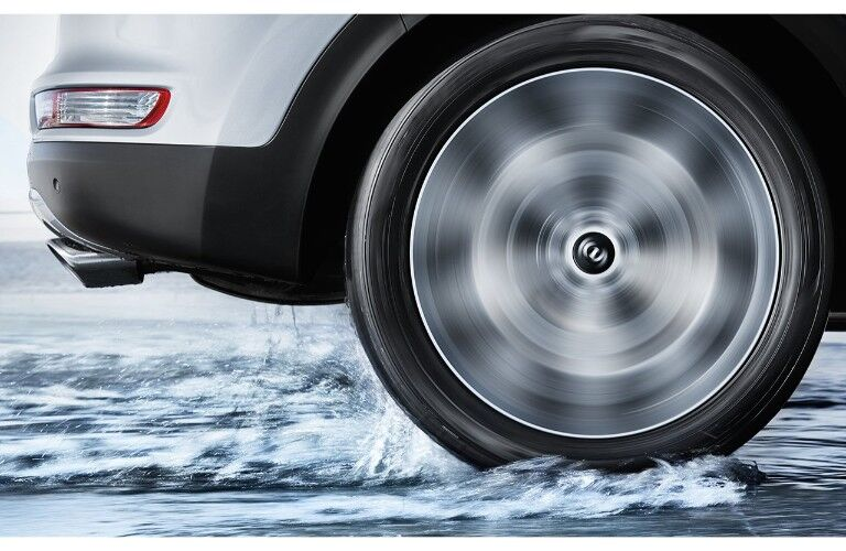 2019 Kia Sportage close up of front wheel spinning on a snow covered icy terrain