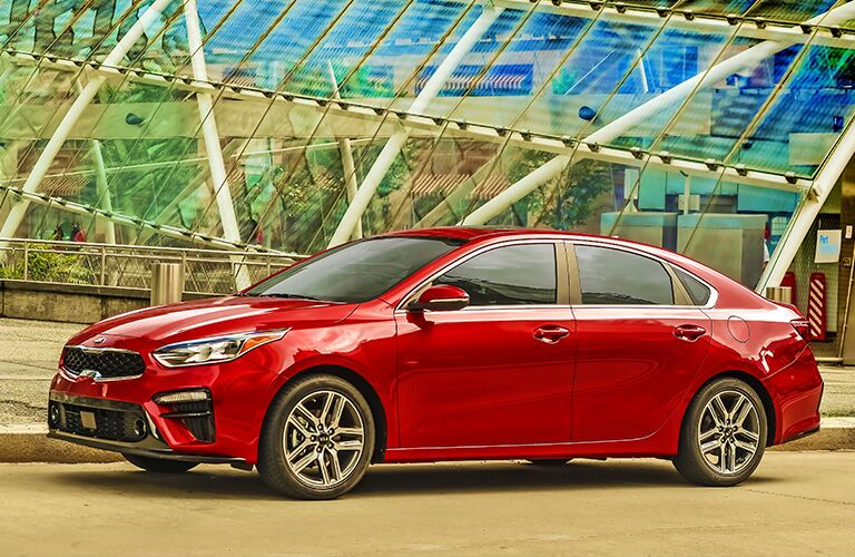 2020 Kia Forte exterior side shot with red paint color parked outside a glass panel dome