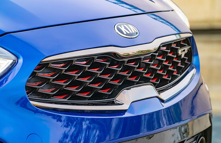 2020 Kia Forte GT with blue paint color exterior front closeup of grille with red accents and GT badge