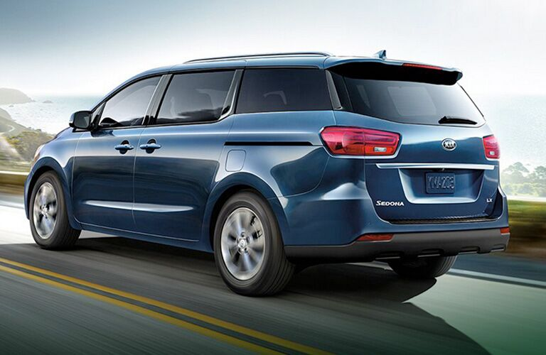 2020 Kia Sedona exterior side rear shot with blue paint color driving on a country highway