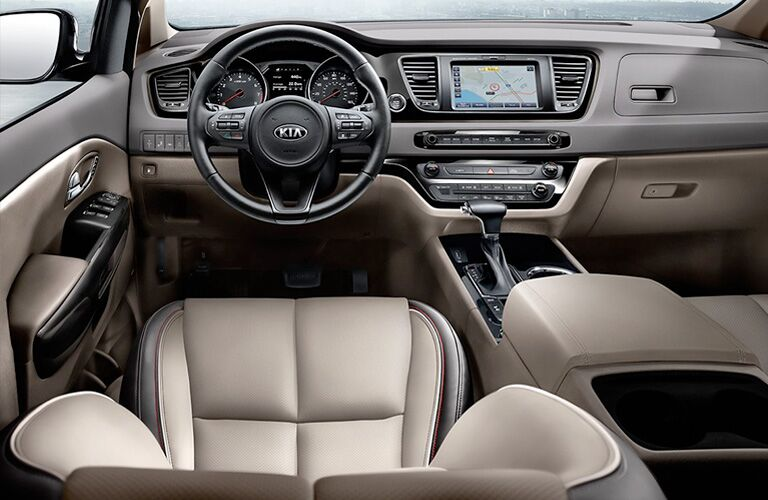 2021 Kia Sedona minivan interior shot of front seating, steering wheel, transmission, and dashboard layout