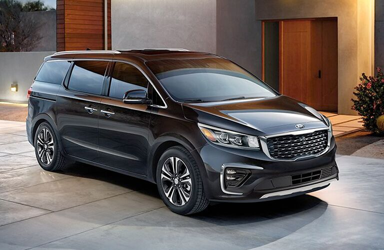 2020 Kia Sedona exterior shot with black paint color parked on a plaza outside of a luxury home