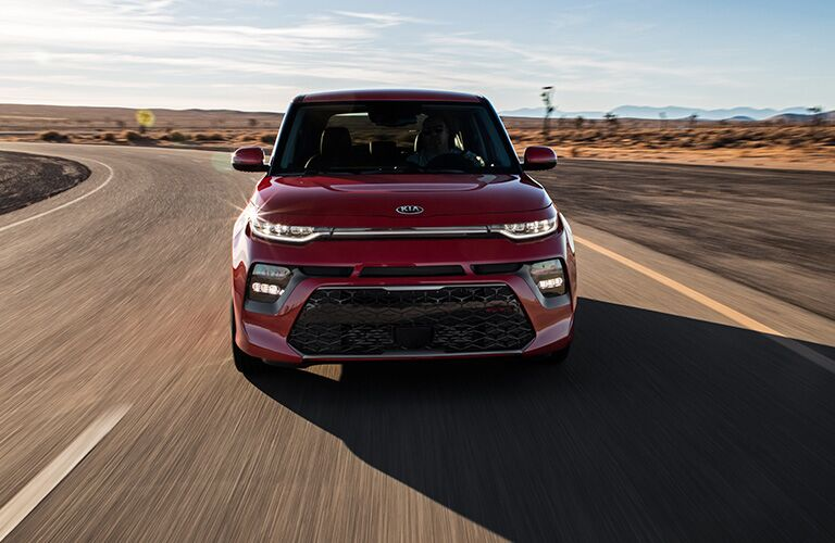 2020 Kia Soul exterior front shot with red paint color driving down a desert highway