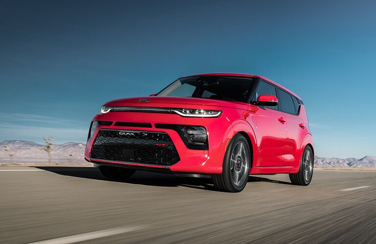 2020 Kia Soul exterior shot with red paint color driving down a road with an open cloudless blue sky behind it