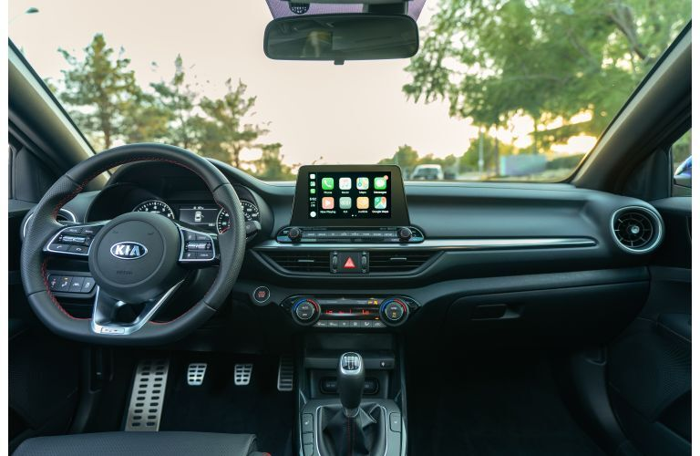 2020 Kia Forte GT interior shot of front seating, steering wheel, dashboard display screen, and accents